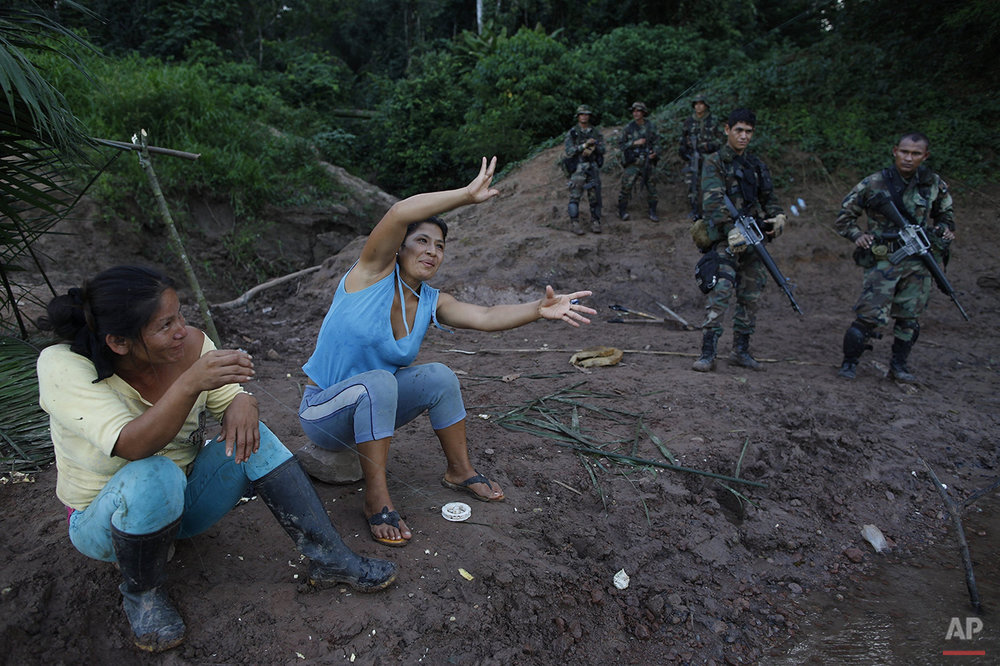 In this July 31, 2015 photo, women fish in the Palcazu River while counternarcotics special forces police wait for their comrades after destroying an airstrip in the Peruvian jungle, used by drug traffickers near Ciudad Constitucion, Peru. The police located the landing strip with a GPS receiver. (AP Photo/Rodrigo Abd)