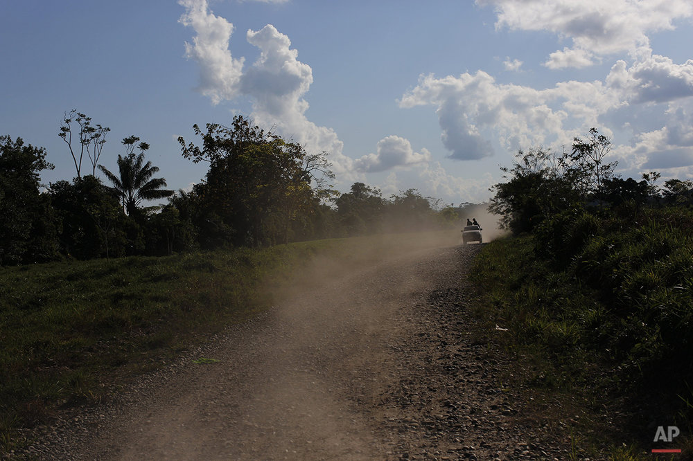 In this July 28, 2015 photo, counternarcotics special forces ride on pick-up truck as they head to blow a hole in a clandestine airstrip used by drug traffickers near Ciudad Constitucion, Peru. The task force left base in three trucks, then forded streams and hiked for 2 hours in the dense jungle before making it to their target destination. (AP Photo/Rodrigo Abd)