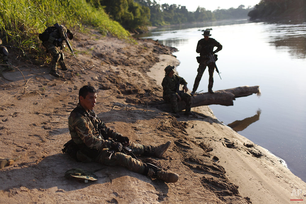 In this July 31, 2015 photo, counternarcotics police officer Merlin Gonzales, 27, takes a break as he sits on the sandy back of the Palcazu River, while he waits with his comrades for the boat that will carry them back to their base in Ciudad Constitucion, Peru. The officers have just marched hours through the jungle after cratering a clandestine runway used by cocaine traffickers in the Peruvian jungle. (AP Photo/Rodrigo Abd)