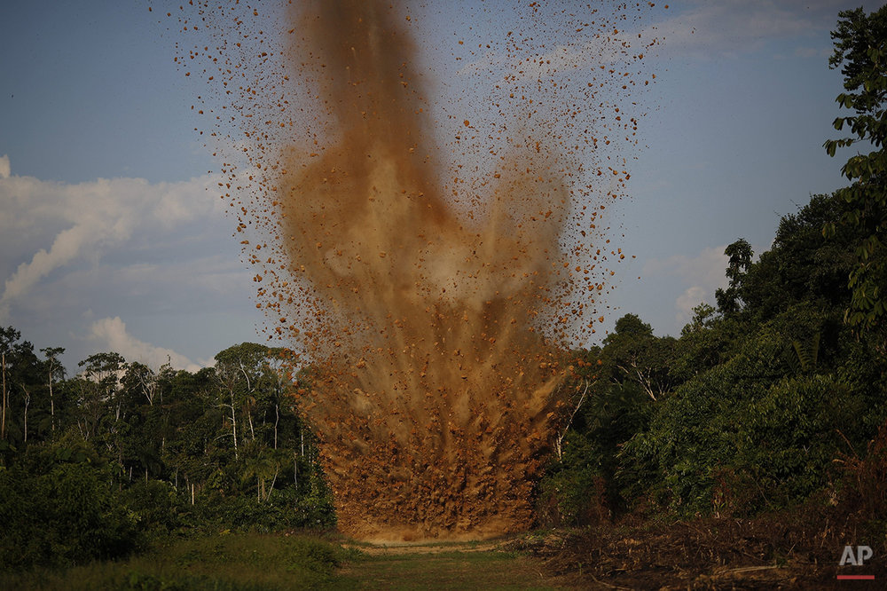 In this July 31, 2015 photo, dirt is blasted skywards as a clandestine airstrip is cratered with explosives by Peruvian counternarcotics forces, in the jungle near Ciudad Constitucion, Peru. According to police, the airstrip is used by drug traffickers to ship cocaine to neighboring Bolivia.  (AP Photo/Rodrigo Abd)