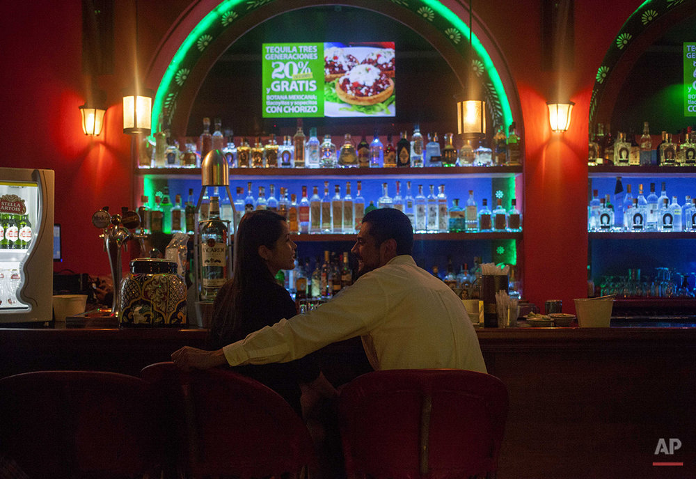 In this Aug. 21, 2015 photo, a couple sits in the upstairs bar at the Tenampa Salon in Mexico City. Located in Mexico City's Plaza Garibaldi, the restaurant and bar has attracted visitors for 90 years from across Mexico and from around the world. (AP Photo/Sofia Jaramillo)