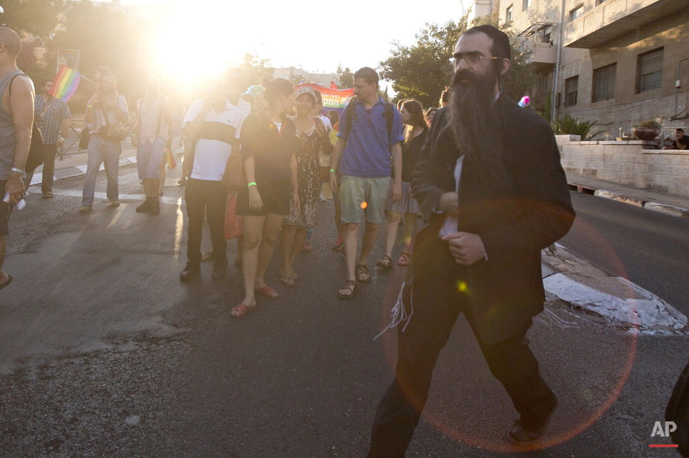 Ultra-Orthodox Jew Yishai Schlissel walks through a Gay Pride parade and is just about to pull a knife from under his coat and start stabbing people in Jerusalem Thursday, July 30, 2015. Schlissel was recently released from prison after serving a term for stabbing several people at a gay pride parade in 2005.(AP Photo/Sebastian Scheiner)