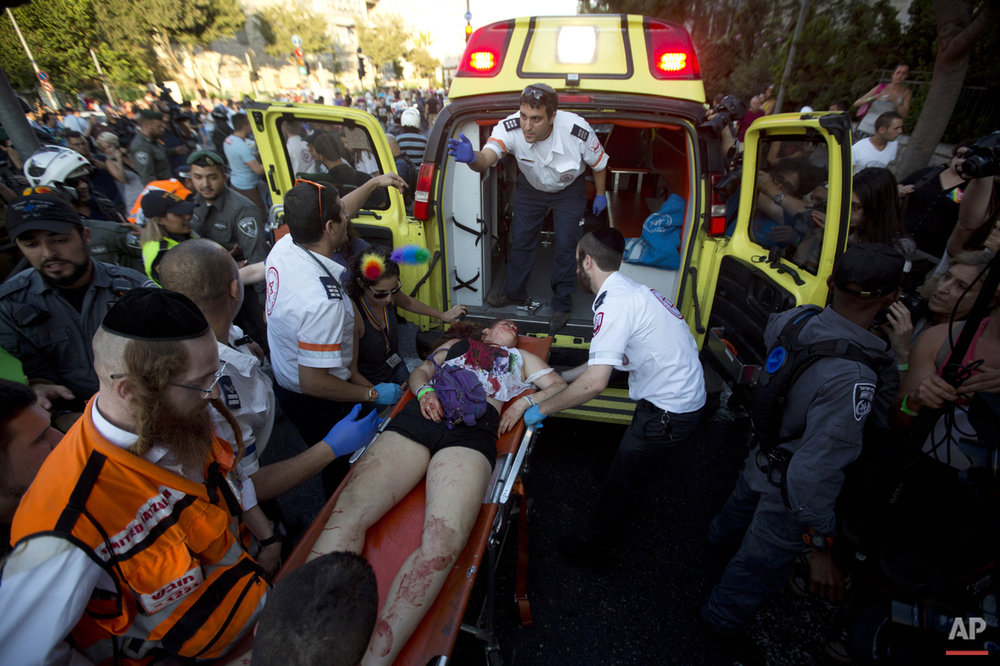 Paramedics roll a wounded person into an ambulance after an ultra-Orthodox Jew attacked people with a knife during a Gay Pride parade Thursday, July 30, 2015 in Jerusalem.  (AP Photo/Sebastian Scheiner)