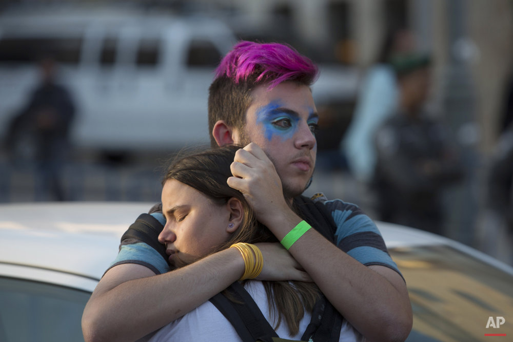 People react after an ultra-Orthodox Jew attacked people with a knife during a Gay Pride parade Thursday, July 30, 2015 in Jerusalem.  (AP Photo/Sebastian Scheiner)
