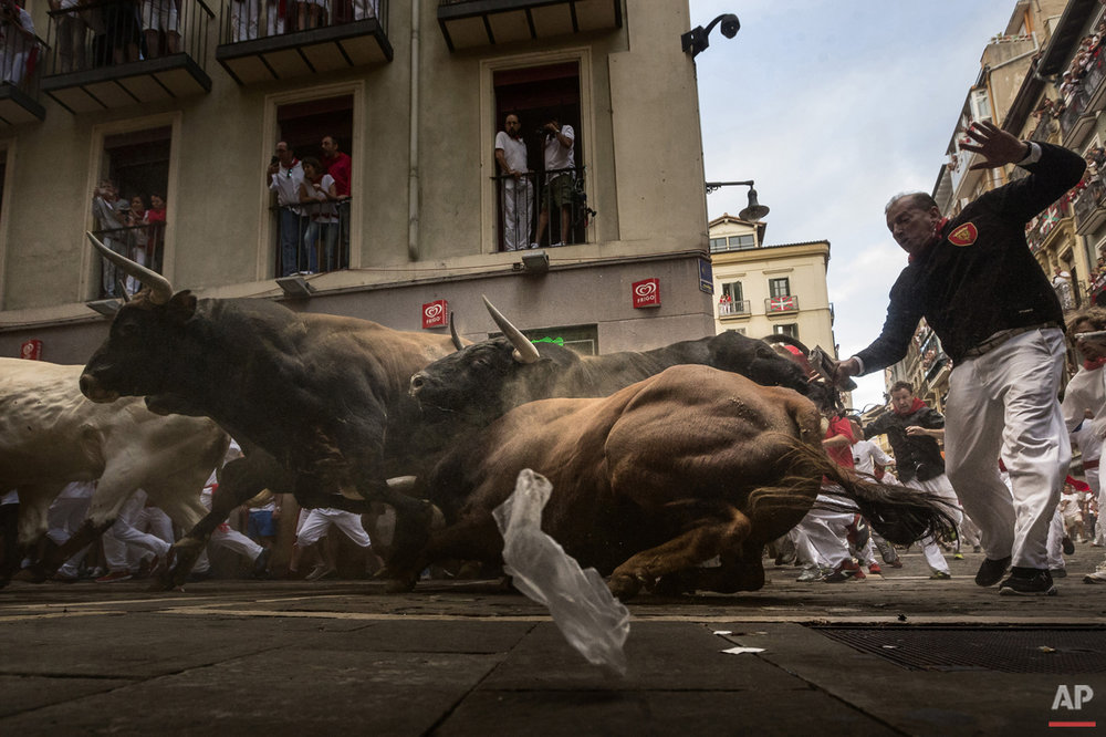 Revelers run chased by 'El Tajo y La Reina' ranch fighting bulls as they turn Estafeta corner during a running of the bulls of the San Fermin festival in Pamplona, Spain.  (AP Photo/Daniel Ochoa de Olza)
