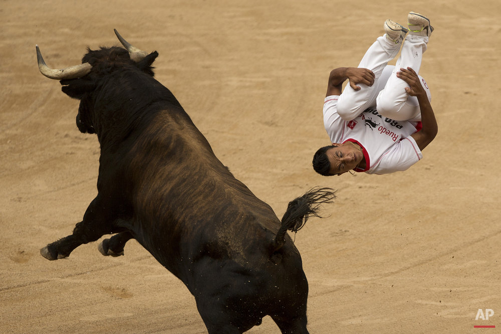 A ''recortador'' jumps over a bull during a competition at the San Fermin festival in Pamplona, Spain, Saturday, July 11, 2015.  (AP Photo/Andres Kudacki)