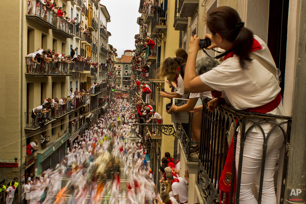 People watch as El Tajo y La Reina fighting bulls and revelers run during the running of the bulls, at the San Fermin festival, in Pamplona, Spain, Wednesday, July 8, 2015. (AP Photo/Andres Kudacki)