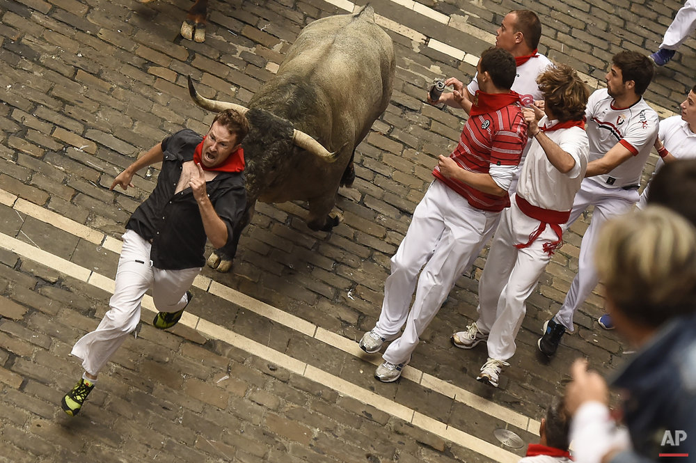 A participant runs in front of a ''Jose Escolar Gil'' fighting bull alongside Mercaderes street, during the fifth running of the bulls, at the San Fermin Festival, in Pamplona, Spain, Saturday, July 11, 2015.  (AP Photo/Alvaro Barrientos)