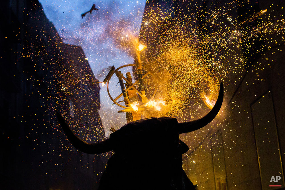 "A flaming fake bull known as a ""Toro de fuego"" runs after revelers during San Fermin festival in Pamplona, Spain, Monday, July 13, 2015. (AP Photo/Andres Kudacki)"
