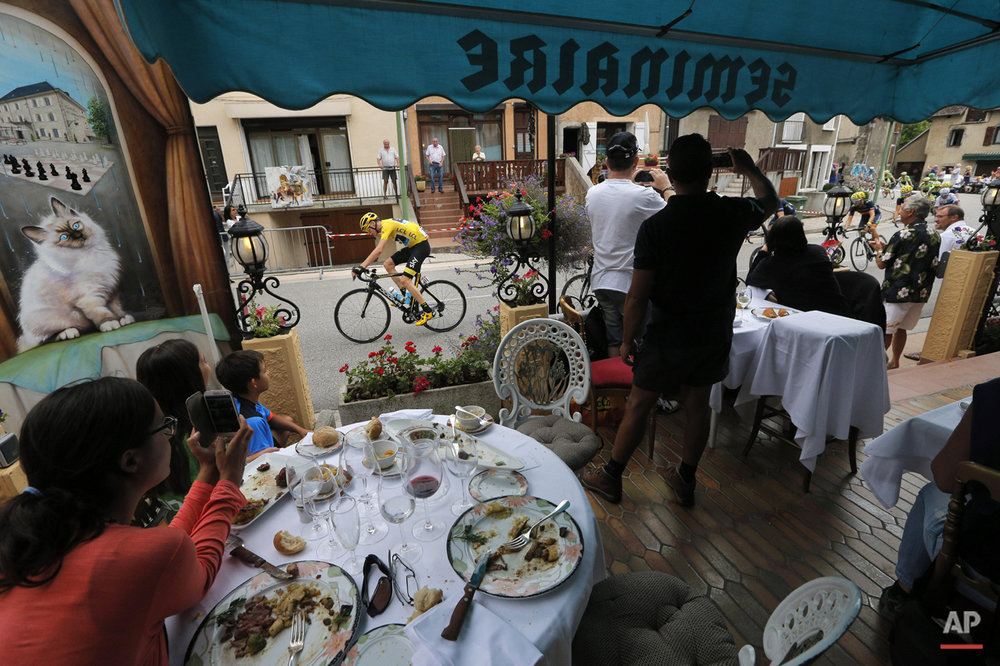 Clients watch from the terrace of a restaurant as the pack with Britain's Chris Froome, wearing the overall leader's yellow jersey, passes during the eighteenth stage of the Tour de France cycling race over 186.5 kilometers (115.9 miles) with start in Gap and finish in Saint-Jean-de-Maurienne, France, Thursday, July 23, 2015. (AP Photo/Christophe Ena)