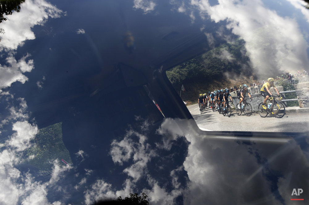 Clouds reflect in a car window as the pack with Britain's Chris Froome, wearing the overall leader's yellow jersey, passes during the nineteenth stage of the Tour de France cycling race over 138 kilometers (85.7 miles) with start in Saint-Jean-de-Maurienne and finish in La Toussuire, France, Friday, July 24, 2015. (AP Photo/Laurent Cipriani)