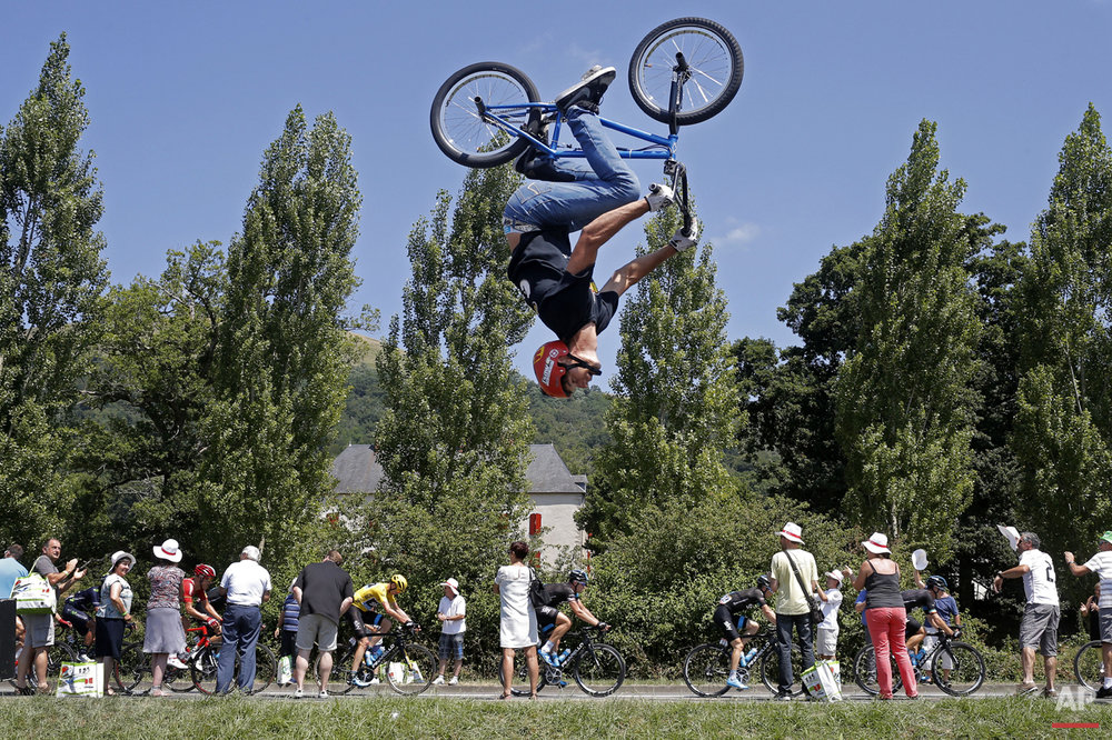 A man performs a BMX bike stunt as the pack with Britain's Christopher Froome, wearing the overall leader's yellow jersey, passes during the tenth stage of the Tour de France cycling race over 167 kilometers (103.8 miles) with start in Tarbes and finish in La Pierre-Saint-Martin, France, Tuesday, July 14, 2015. (AP Photo/Laurent Cipriani)