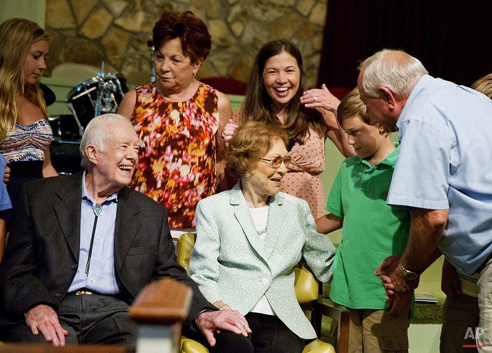 Former President Jimmy Carter, left, sits with his wife Rosalynn as they pose for photos with Bill Bush, of Adel, Ga., from right, his grandson Carson Shirley, 9, daughter Lara Norris, and wife Pat Bush after Carter taught Sunday School class at Maranatha Baptist Church in his hometown Sunday, Aug. 23, 2015, in Plains, Ga. The 90-year-old Carter gave one lesson to about 300 people filling the small Baptist church that he and his wife, Rosalynn, attend. It was Carter's first lesson since detailing the intravenous drug doses and radiation treatment planned to treat melanoma found in his brain after surgery to remove a tumor from his liver. (AP Photo/David Goldman)