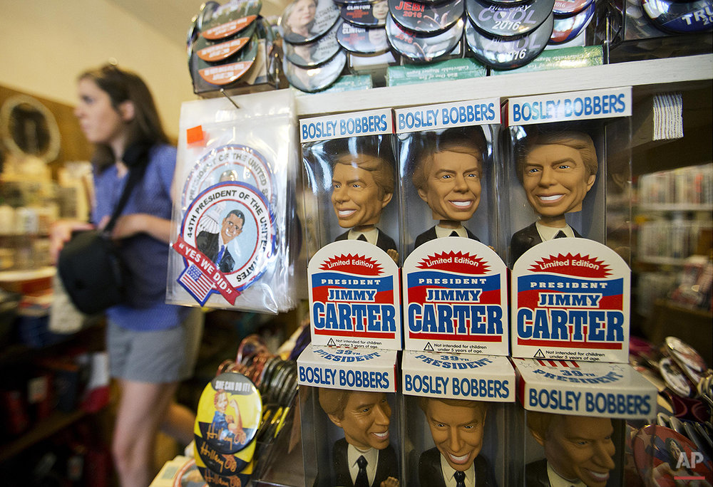 A person walks near dolls of former President Jimmy Carter in a store in his hometown of Plains, Ga., Saturday, Aug. 22, 2015, The one-block business district specializes in Carter political memorabilia and peanut souvenirs. Visitors stop by after touring dozens of properties associated with the Nobel Peace Prize winner. (AP Photo/David Goldman)