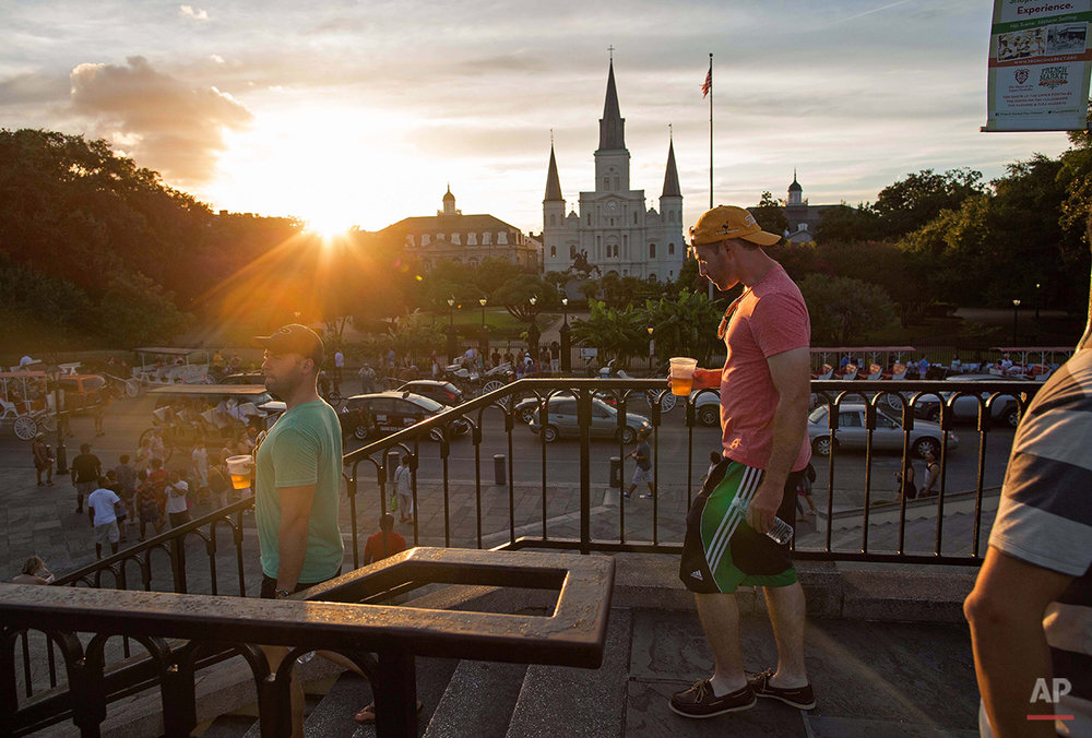 Visitors holding cups of beer walk down stairs on Jackson Square in the heart of the French Quarter of New Orleans, Saturday, Aug. 15, 2015. New Orleans is nearly three centuries old, mixing African-American, French, Spanish and Caribbean traditions to create unique forms of music, food and culture found nowhere else in America. (AP Photo/Max Becherer)