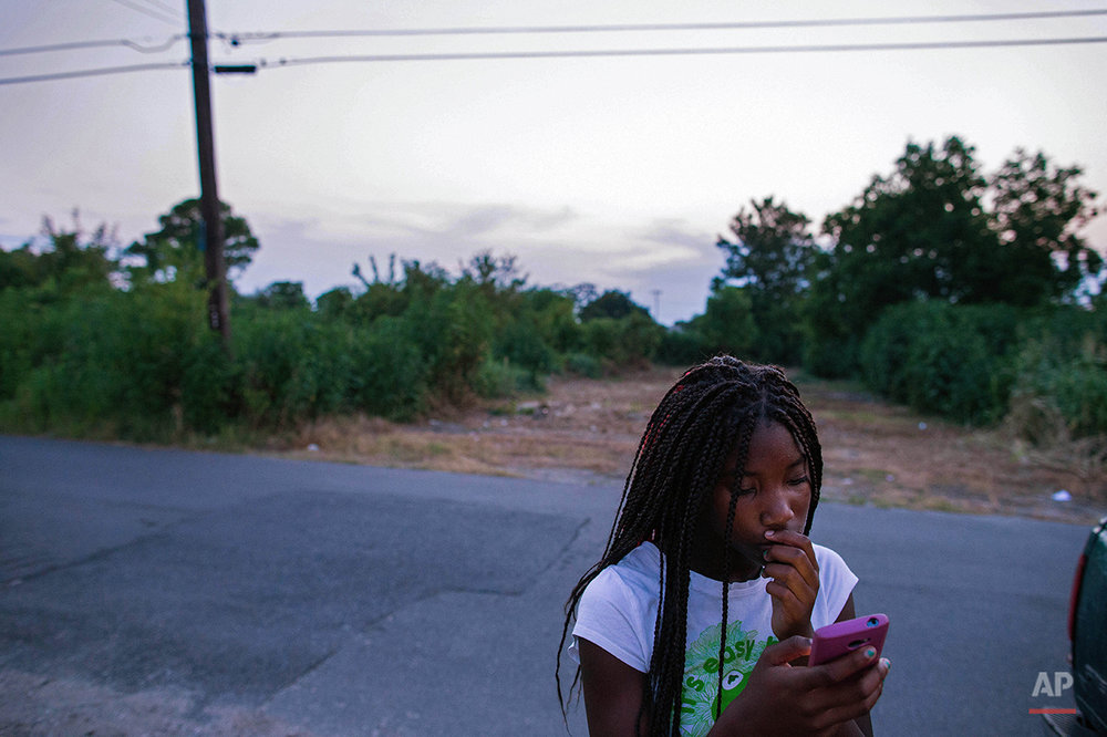 Marquell Williams, 12, uses her phone to view videos on Facebook in the Lower 9th Ward of New Orleans, Friday, Aug. 14, 2015. Williams survived Katrina with her family in Mississippi and moved to New Orleans after the storm. (AP Photo/Max Becherer)