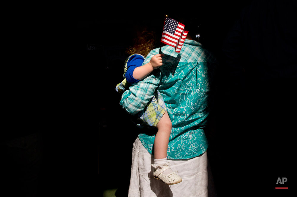 Davonna Clyde, of Sarver, Pa., holds her daughter Lauren Clyde as they stand in a shaft of light while waiting for the arrival of former Pennsylvania Sen. Rick Santorum, for his announcement that he is entering the Republican presidential race, Wednesday, May 27, 2015, in Cabot, Pa. (AP Photo/Jacquelyn Martin)