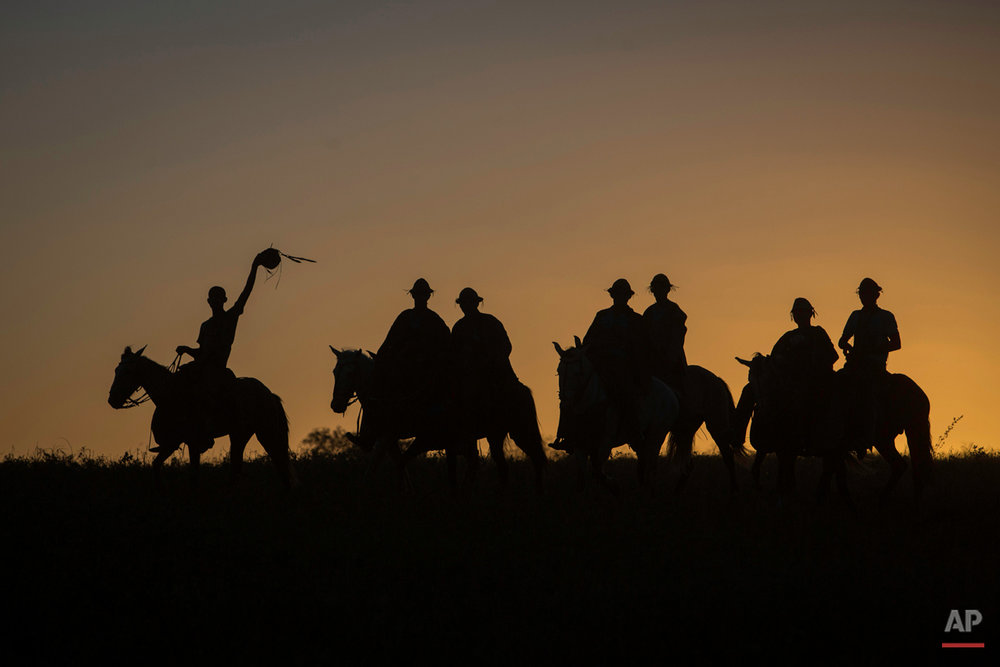 """In this July 24, 2015 photo, cowboys ride home at sunset after competing in the annual Catch the Bull event known as """"Pega do Boi"""" in Serrita, in Brazil's Pernambuco state. Brazilian cowboys, known as """"vaqueiros,"""" are traditionally from this northeastern region, and emerged from the integration of white colonizers with native Brazilian indigenous communities around the 15th century, when cattle and horses were introduced to Brazil. (AP Photo/Eraldo Peres)"""