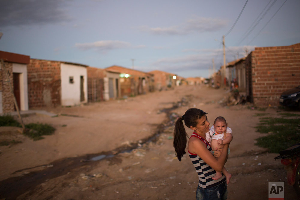 Angelica Pereira holds her daughter Luiza, who was born with microcephaly, outside her house in Santa Cruz do Capibaribe, Pernambuco state, Brazil, Saturday, Feb. 6, 2016. The Zika virus, spread by the Aedes aegypti mosquito, thrives in people's homes and can breed in even a bottle cap's-worth of stagnant water. The virus is suspected to be linked with occurrences of microcephaly in new born babies, but no link has been proven yet. (AP Photo/Felipe Dana)