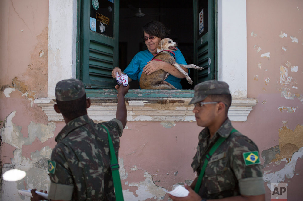 "Brazilian Army soldiers distribute flyers with information on how to combat the Aedes aegypti during the ""Burial of the Mosquito"" carnival block parade in Olinda, Pernambuco state, Brazil, Friday, Feb. 5, 2016. The parade that happens every year during carnival informs residents and tourists about the dangers of the Aedes aegypti and teaches them how to combat the mosquitoes. (AP Photo/Felipe Dana)"