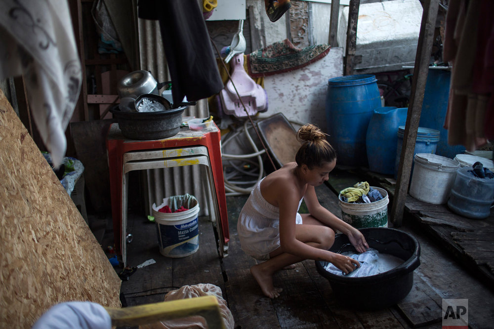 Marilia da Silva, 14, washes clothes near water storage containers, potential mosquito breeding sites, outside her house in a slum of Recife, Brazil, Friday, Feb. 5, 2016. The Zika virus, spread by the Aedes aegypti mosquito, thrives in people's homes and can breed in even a bottle cap's-worth of stagnant water. Public health experts agree that the poor are more vulnerable because they often lack amenities that help diminish the risk. (AP Photo/Felipe Dana)