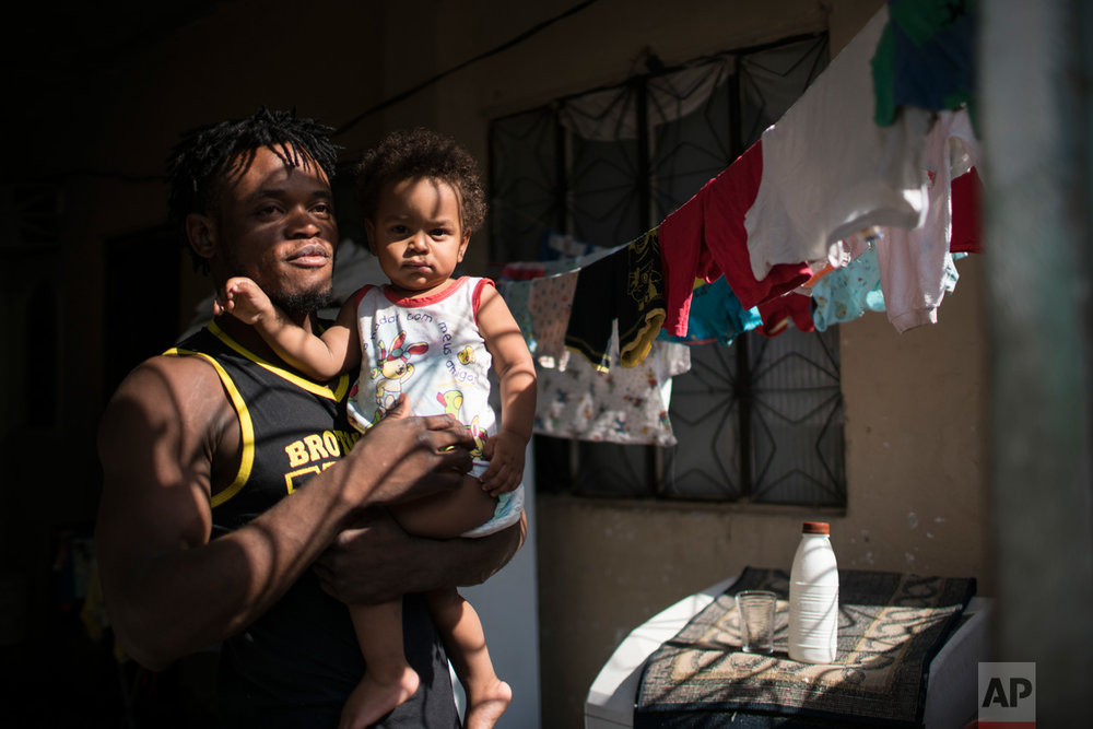 In this May 27, 2016 photo, Popole Misenga, a refugee and judo athlete from the Democratic Republic of Congo who hopes to make the cut for the first Olympic team of refugee athletes, holds his one-year-old son Elias at their home in Rio de Janeiro, Brazil. Misenga fled his war-torn hometowns as a child. Civil strife in the central African nation has caused the deaths of several million people since the mid-1990s. (AP Photo/Felipe Dana)