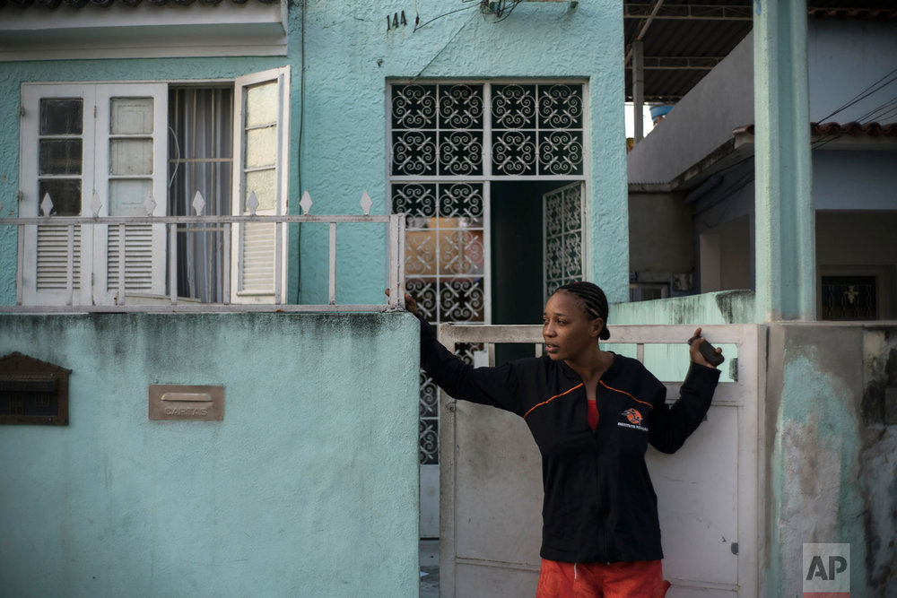 In this May 28, 2016 photo, Yolande Mabika, a refugee and judo athlete from the Democratic Republic of Congo who hopes to join the first Olympic team of refugee athletes, stands at the entrance of her newly rented apartment in Rio de Janeiro, Brazil. A member of Congo's national judo federation, Mabika says that training was harsh and failure to win medals meant punishments, including stints inside a cell with little food or water for days. (AP Photo/Felipe Dana)