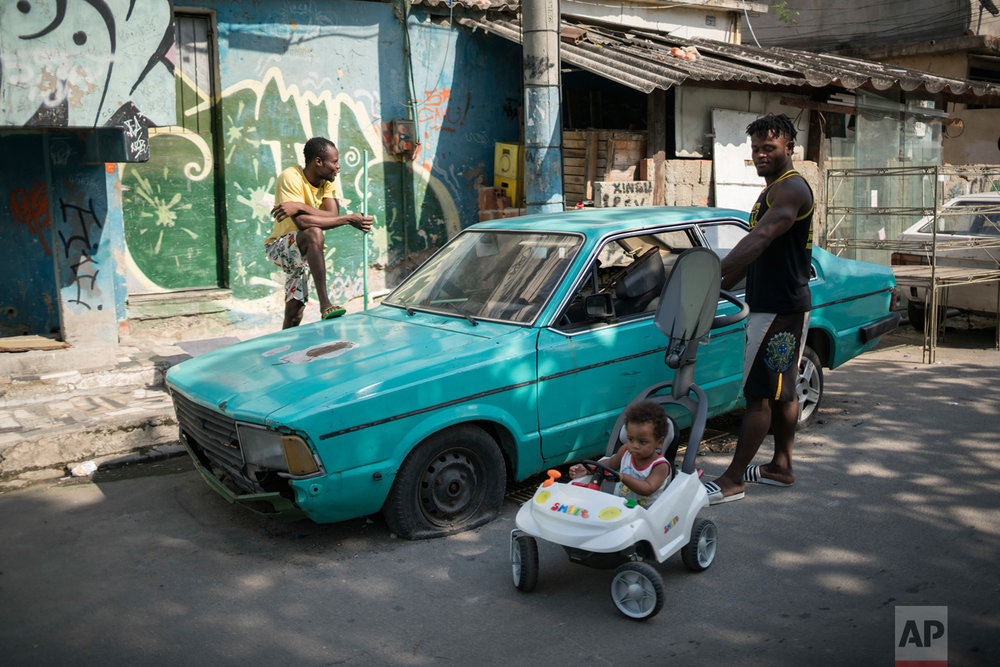 In this May 27, 2016 photo, Popole Misenga, a refugee and judo athlete from the Democratic Republic of Congo who hopes to make the cut for the Olympics first refugee team, talks to a Congolese neighbor as he walks with his one-year-old son Elias in Rio de Janeiro, Brazil. The International Olympic Committee is expected to name members of the Team Refugee Olympic Athletes during its June 1 - 3 meeting. The team will compete under the Olympic flag instead of any one country. (AP Photo/Felipe Dana)