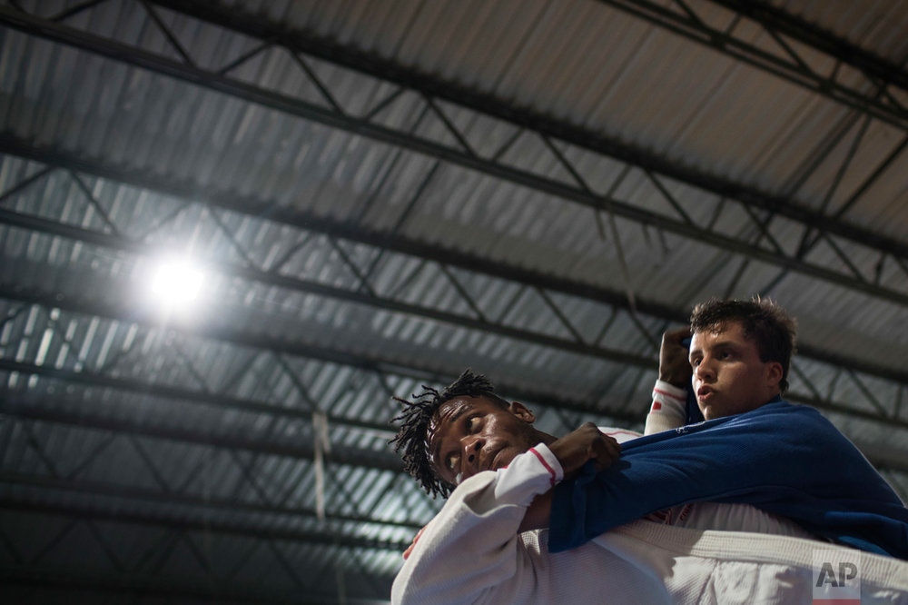 In this May 27, 2016 photo, Popole Misenga, a refugee from the Democratic Republic of Congo, left, practices judo in hopes of making the cut for an Olympic team of refugee athletes, at the Reacao Institute in Rio de Janeiro, Brazil. With the help of the Reacao charity, Misenga has daily judo classes and cross-training just like Brazilian athletes preparing for the Olympics. (AP Photo/Felipe Dana)