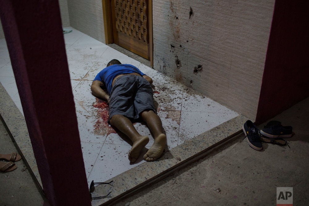 This July 13, 2016 photo shows the body of a man who was taken from the inside of his home and shot dead at the entrance of his home in Nova Iguacu, greater Rio de Janeiro, Brazil. Scenes of impunity and violence play out daily in many of Rio's hundreds of slums, known here as favelas, and other outlying areas. Police believe this homicide was gang-related. (AP Photo/Felipe Dana)