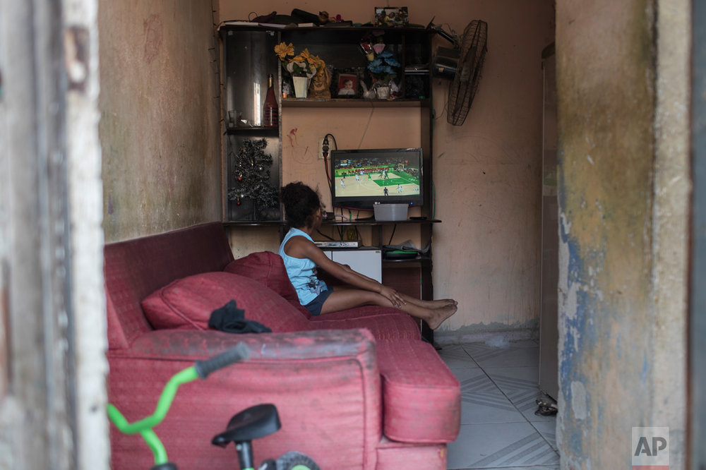 A girl watches on a television the men's basketball game between Brazil and Spain at the 2016 Summer Olympics in Rio de Janeiro, Brazil, Tuesday, Aug. 9, 2016. (AP Photo/Felipe Dana)