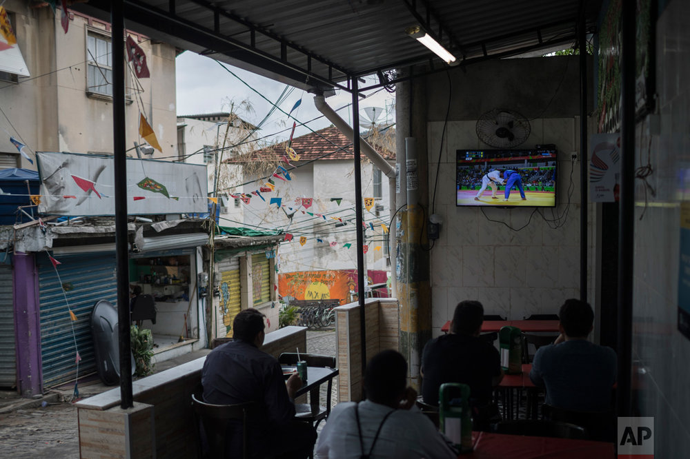 People watch on a television the men's judo competition at at the 2016 Summer Olympics as they sit for lunch at the Dona Marta slum in Rio de Janeiro, Brazil, Wednesday, Aug. 10, 2016. (AP Photo/Felipe Dana)