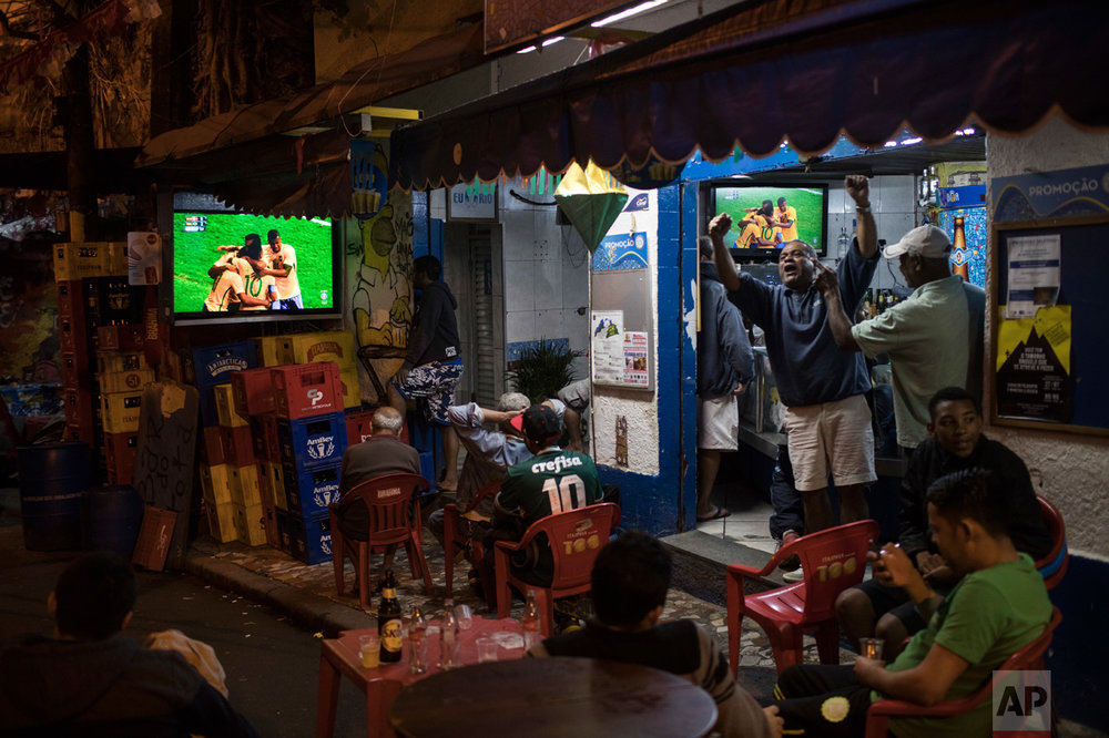 People celebrate after Brazil scored a goal against Denmark during the men's Olympic football tournament at the 2016 Summer Olympics while watching the live transmission at a bar in Rio de Janeiro, Brazil, Wednesday, Aug. 10, 2016. (AP Photo/Felipe Dana)
