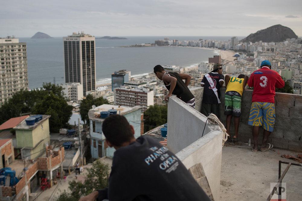 Boys look at kites atop the Babilonia slum, overlooking Copacabana beach in Rio de Janeiro, Brazil, Wednesday, Aug. 3, 2016. (AP Photo/Felipe Dana)