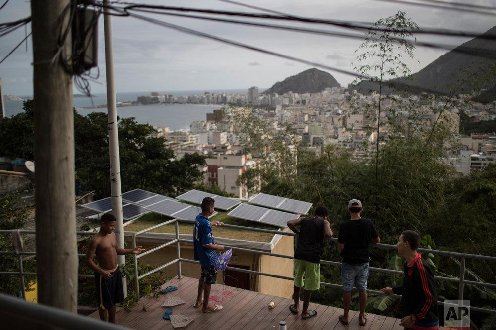Boys prepare to fly their kites atop the Babilonia slum, overlooking Copacabana beach in Rio de Janeiro, Brazil, Wednesday, Aug. 3, 2016. (AP Photo/Felipe Dana)