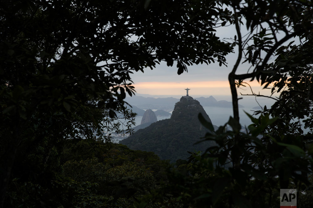The Christ the Redeemer statue and Sugar Loaf mountain are pictured between trees as the sun rises in Rio de Janeiro, Brazil, Thursday, Aug. 4, 2016. (AP Photo/Felipe Dana)