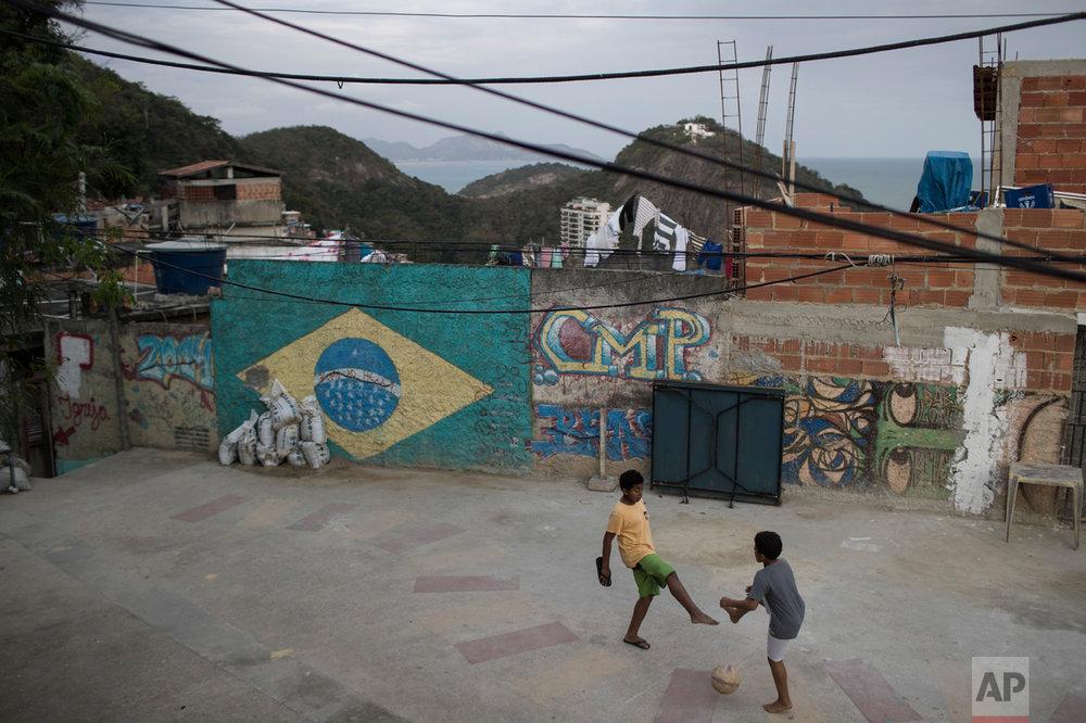 Boys play soccer at the Babilonia slum, overlooking Copacabana beach in Rio de Janeiro, Brazil, Wednesday, Aug. 3, 2016.  (AP Photo/Felipe Dana)
