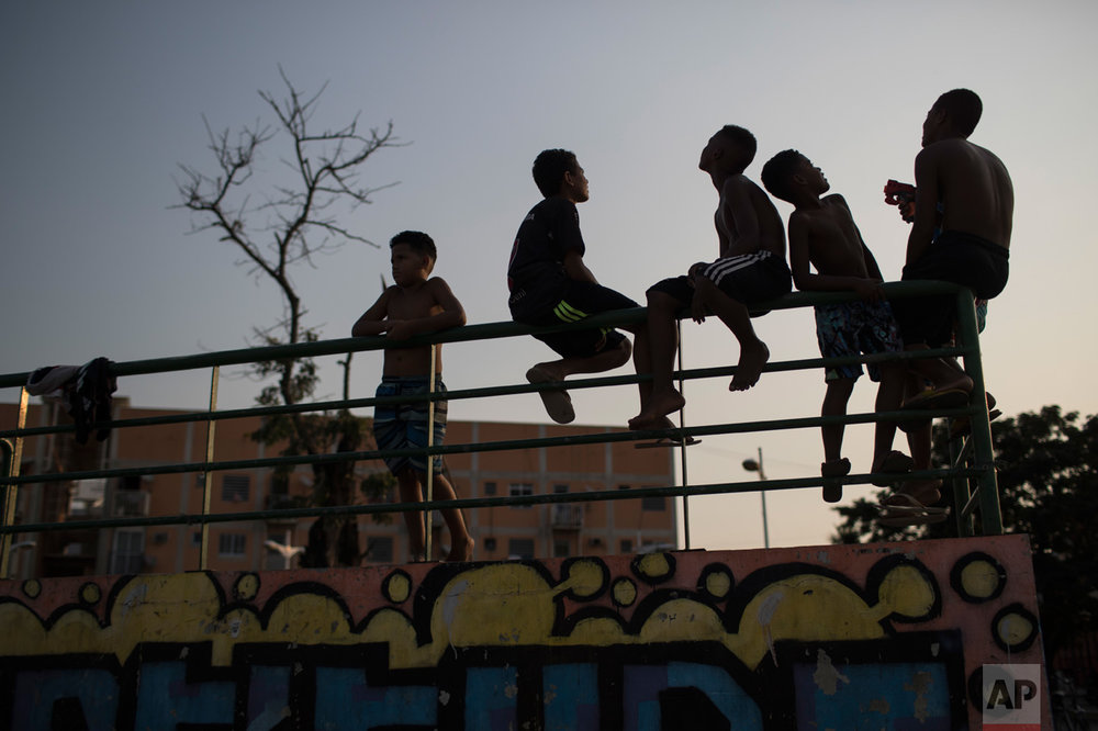 Boys look up at flying kites at the manguinhos slum during the 2016 Summer Olympics in Rio in Rio de Janeiro, Brazil, Tuesday, Aug. 9, 2016. (AP Photo/Felipe Dana)