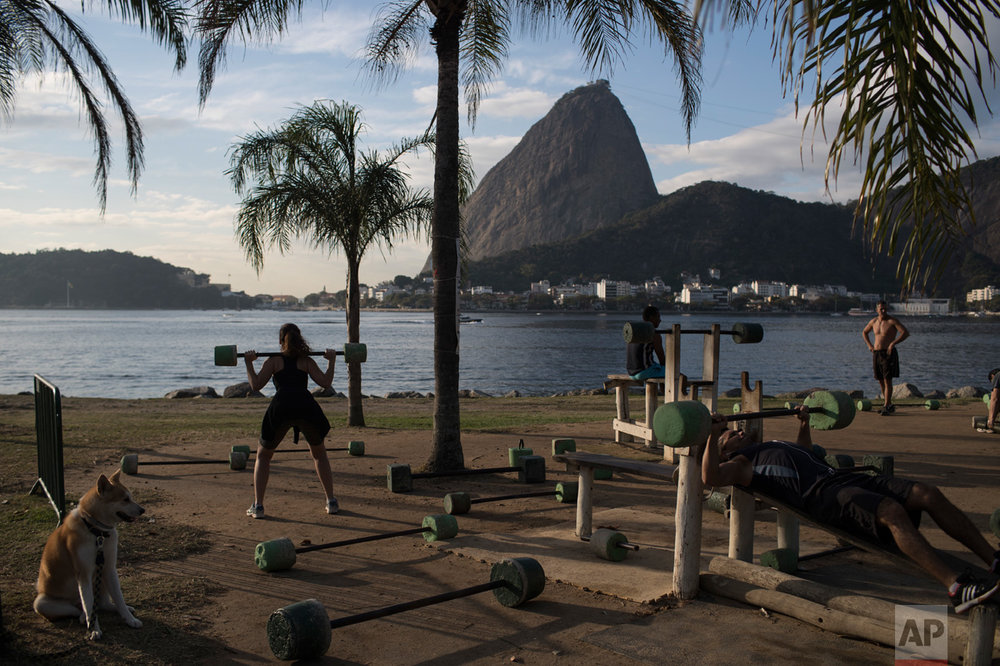 People exercise at an outdoor gym on the shores of Guanabara Bay, where sailing competitions are taking place at the 2016 Summer Olympics in Rio de Janeiro, Brazil, Thursday, Aug. 11, 2016. (AP Photo/Felipe Dana)