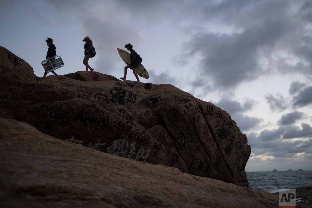 People walk on the rocks of Arpoador beach as the sun sets during the 2016 Summer Olympics in Rio de Janeiro, Brazil, Friday, Aug. 12, 2016. (AP Photo/Felipe Dana)