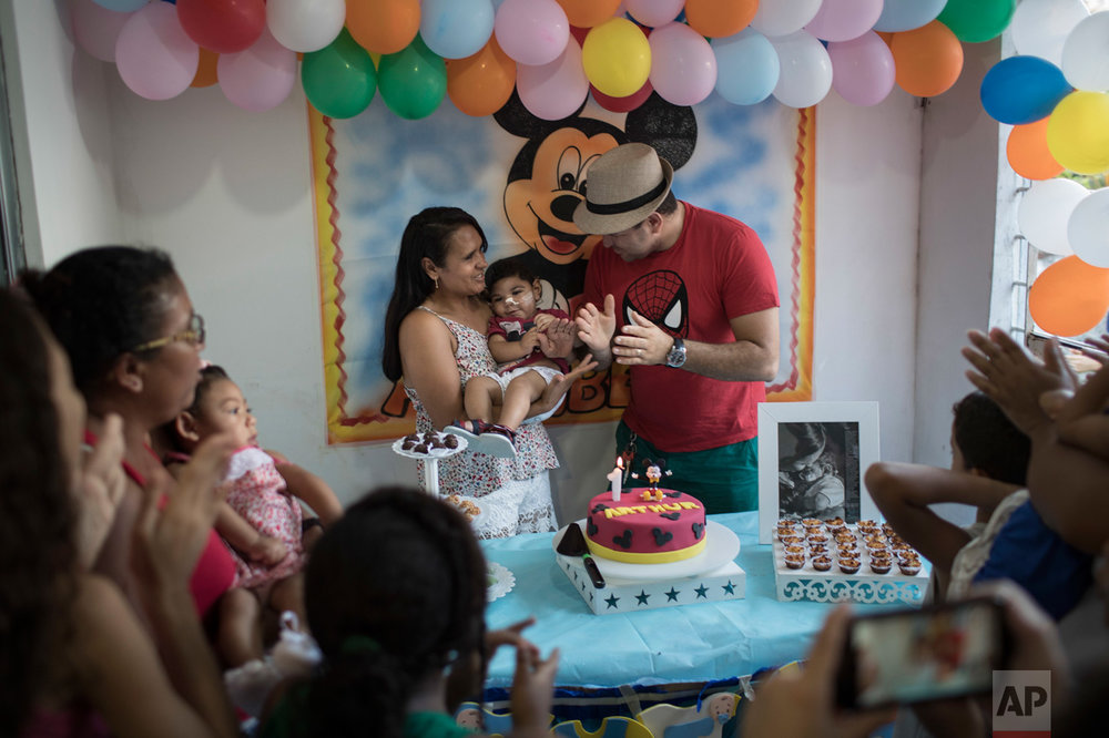 "In this Oct. 1, 2016 photo, Rozilene Ferreira and her husband Elias Rodrigo celebrate the one-year birthday of their son Arthur, who was born with microcephaly, in Recife, Pernambuco state, Brazil. Arthur has started taking high-calorie formula through a tube after he appeared to choke during meals. ""It's every mom's dream to see their child open his mouth and eat well,"" said his mother, adding that each day seems to bring new problems. (AP Photo/Felipe Dana)"