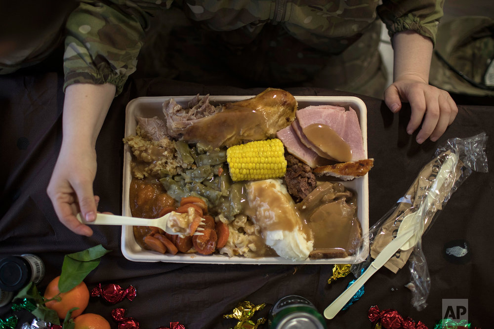 An U.S. Army soldier eats Thanksgiving dinner at a coalition air base in Qayara south of Mosul, Iraq, Thursday, Nov. 24, 2016. (AP Photo/Felipe Dana)