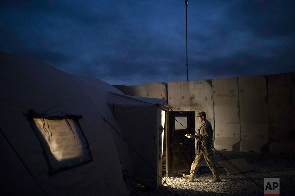 A U.S. Army soldier walks to a tent with his Thanksgiving dinner at a coalition air base in Qayara south of Mosul, Iraq, Thursday, Nov. 24, 2016. (AP Photo/Felipe Dana)