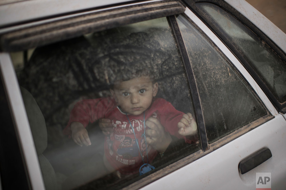 A boy looks out from a car window at a checkpoint near Qayara, south of Mosul, Iraq, Tuesday, Nov. 1, 2016. The U.N. human rights office is lauding efforts by the U.S.-led coalition in the battle against the Islamic State group in Mosul. The office in Geneva says coalition flights over Iraq have largely succeeded in preventing IS from bringing in 25,000 more civilians to the city center, where the militant group has been using people as human shields as Iraqi forces advance on Mosul. (AP Photo/Felipe Dana)