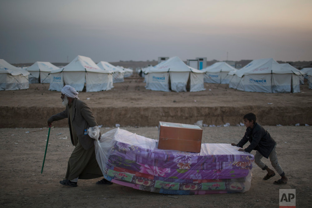 Iraqis displaced by fighting in Mosul carry mattresses at a camp for internally displaced people in Hassan Sham, Iraq, on Tuesday, Nov. 8, 2016. The United Nations says over 34,000 people have been displaced from Mosul, with about three quarters settled in camps and the rest in host communities. (AP Photo/Felipe Dana)