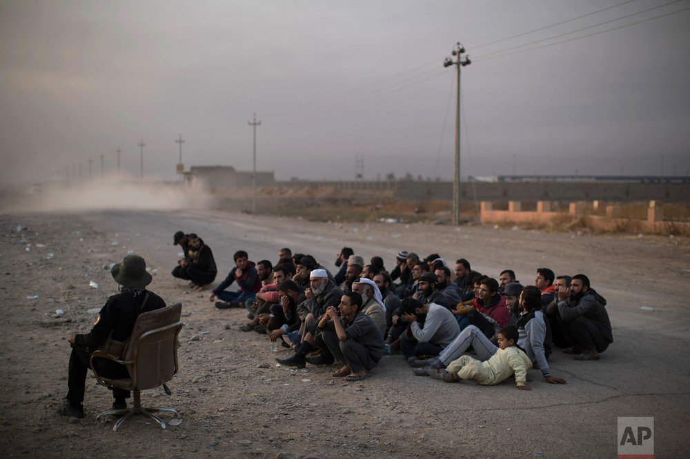 Internally displaced men sit as they wait for their documents to be checked after fleeing fighting between the Iraqi forces and Islamic State, at a checkpoint near Bartella, east of Mosul, Iraq, Monday, Nov. 14, 2016. (AP Photo/Felipe Dana)