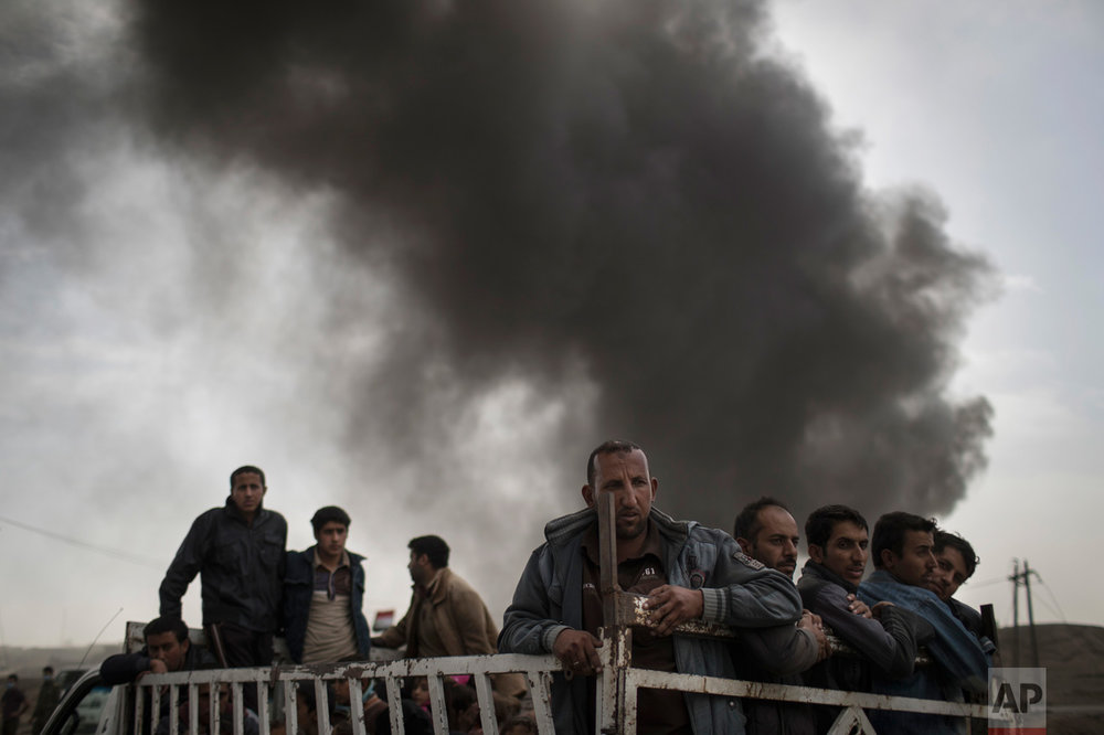 In this Tuesday, Nov. 1, 2016 photo, displaced people stand on the back of a truck at a checkpoint near Qayara, south of Mosul, Iraq. As the operation to retake Mosul enters its second month Iraqi forces are preparing for prolonged, grueling urban combat as they slow the tempo of their operation, advancing just a few hundred meters at a time. The individual tactics employed by IS mirror past fights with the group, but the sheer scale of IS defenses and counterattacks in Mosul has overwhelmed Iraq's military. (AP Photo/Felipe Dana)