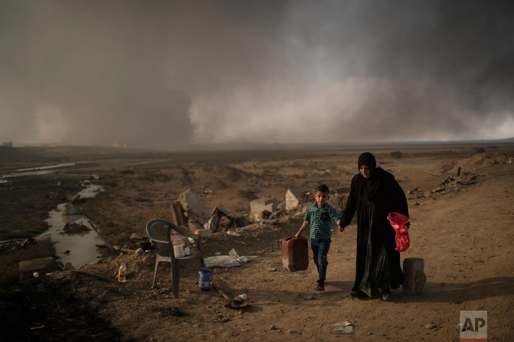 In this Sunday, Nov. 6, 2016 photo, displaced people walk past a checkpoint near Qayara, south of Mosul, Iraq. As the operation to retake Mosul enters its second month Iraqi forces are preparing for prolonged, grueling urban combat as they slow the tempo of their operation, advancing just a few hundred meters at a time. The individual tactics employed by IS mirror past fights with the group, but the sheer scale of IS defenses and counterattacks in Mosul has overwhelmed Iraq's military. (AP Photo/Felipe Dana)