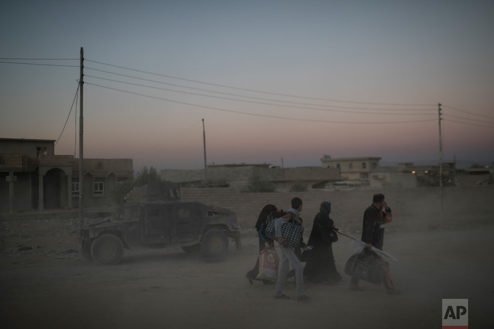 Iraqis flee fighting between Iraqi forces and Islamic State militants on a road in eastern Mosul, Iraq, Friday, Nov. 25, 2016. (AP Photo/Felipe Dana)