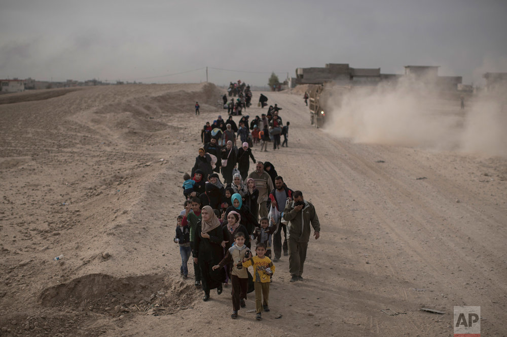 In this Nov. 15, 2016 photo, internally displaced people flee fighting between Iraqi forces and Islamic State militants on a road in eastern Mosul, Iraq. Six weeks into the battle for Mosul, the Iraqi government's 50,000-strong expedition is a long way from finishing the job. The Islamic State is tenaciously defending its last major foothold in Iraq. A million civilians remain inside the city, preventing the use of overwhelming firepower. Iraqi commanders are alarmed that the progress has been lopsided. The battle-seasoned special forces are slowly advancing inside Mosul while other military outfits remain bogged down outside the city. (AP Photo/Felipe Dana)
